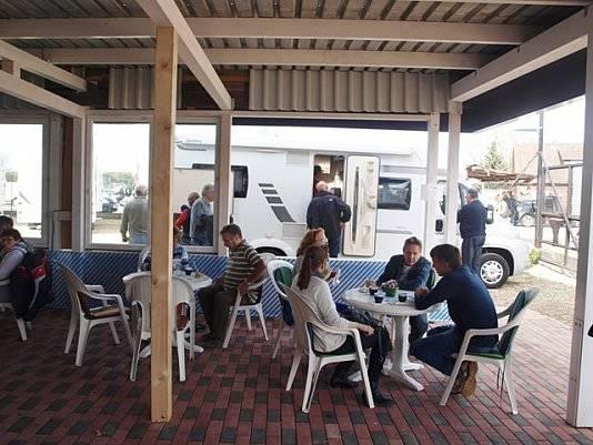 Überdacht sitzen Leute bei Wohnwagen Bodenburg.