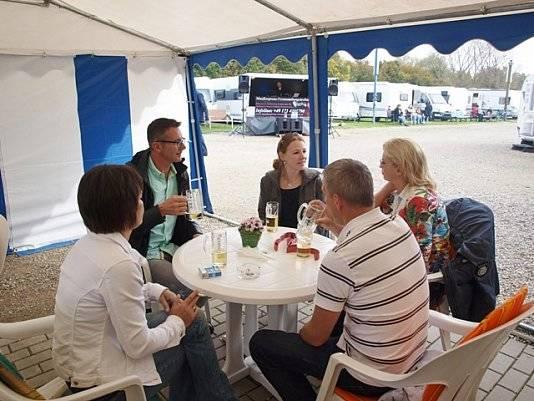 5 Personen sitzen an einem Tisch und unterhalten sich.